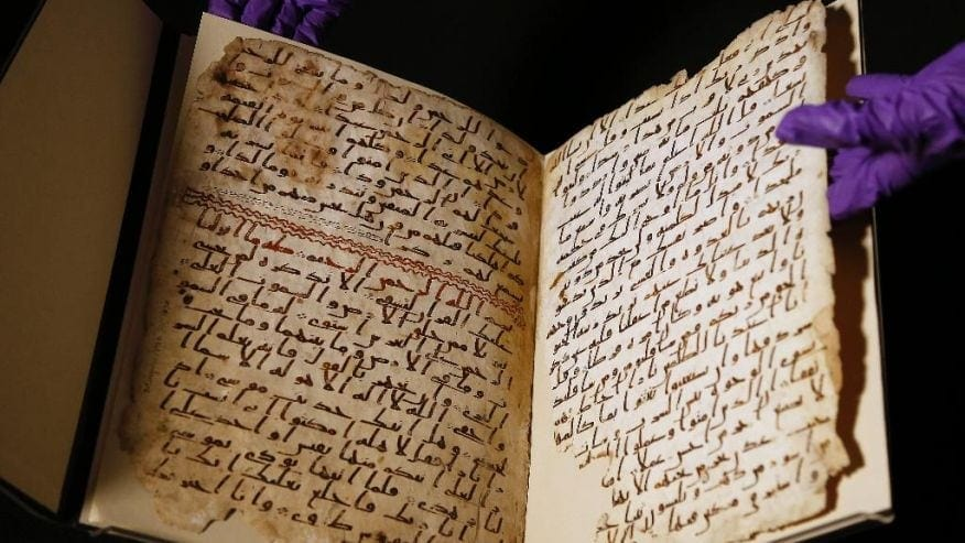 A university assistant shows fragments of an old Qur'an at the University in Birmingham, in Birmingham central England on 22 July, 2015.