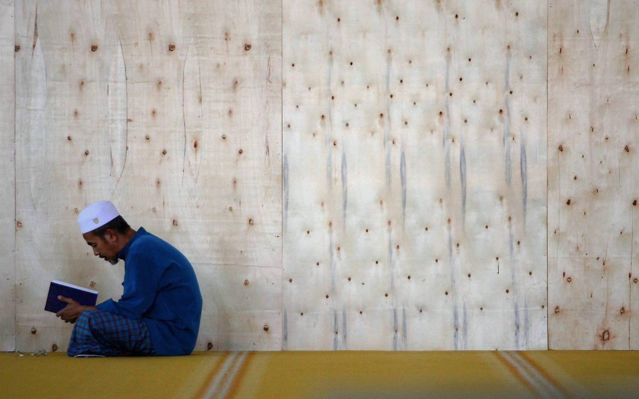 Man reading Quran learning student